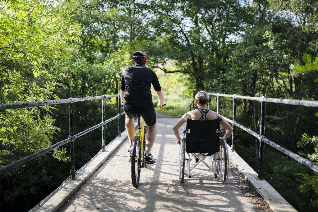 Pariskunta harjoittelemassa pyörällä ja pyörätuolilla