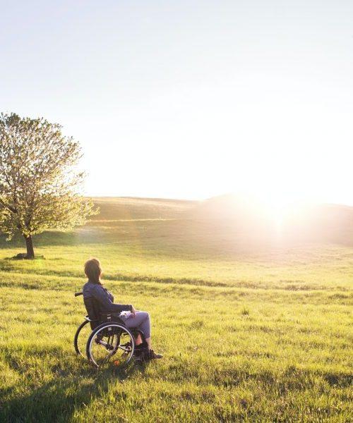 Nainen ihailee auringonlaskua pyörätuolissa, Suomi.