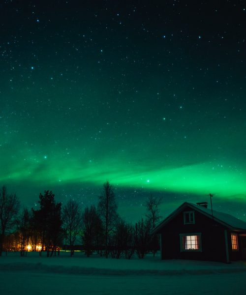 Northern lights (Aurora Borealis) over cottage in Lapland village. Finland